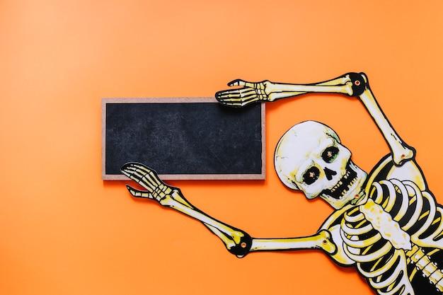 Gespenstisches skelett mit tafel