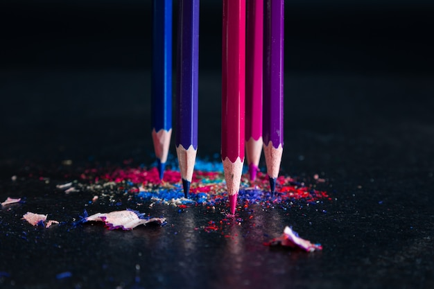 Gespitzte buntstifte stehen aufrecht vor einem dunklen hintergrund in mehrfarbigen spänen von bleistiftminen
