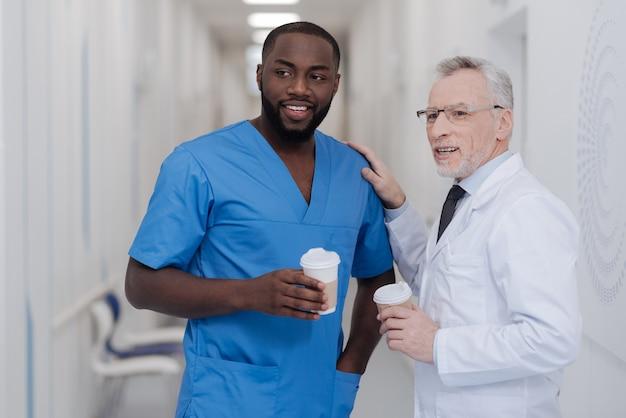 Gespräch mit einem zuverlässigen jungen kollegen. erfreuter professioneller alternder arzt, der in der klinik steht, während er eine tasse kaffee hält und das gespräch mit einem afroamerikanischen kollegen genießt