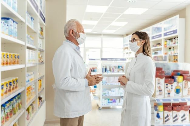 Gespräch zwischen zwei apothekern und dem coronavirus. vor seiner pensionierung unterrichtet der apotheker den jungen apotheker über die arbeit in einer apotheke. sie tragen uniformen und gesichtsmasken