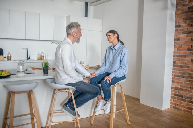 Gespräche in der küche. ein mann und eine frau sitzen in der küche und unterhalten sich