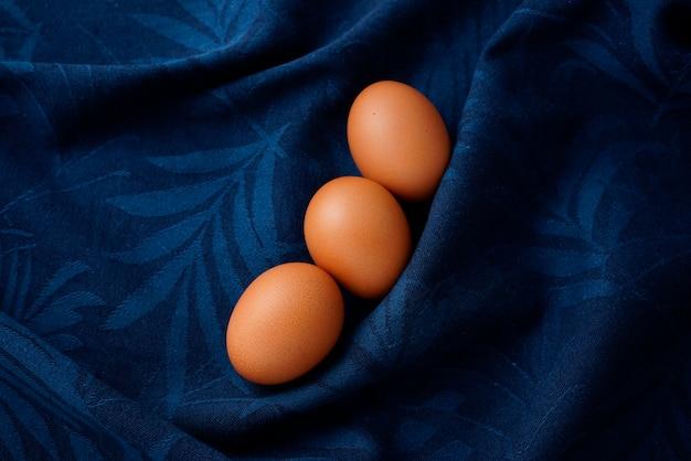 Gesprenkelte braune eier-food-styling auf samtblauem, zerknittertem textur-geschirrtuch-zusammenfassungshintergrund