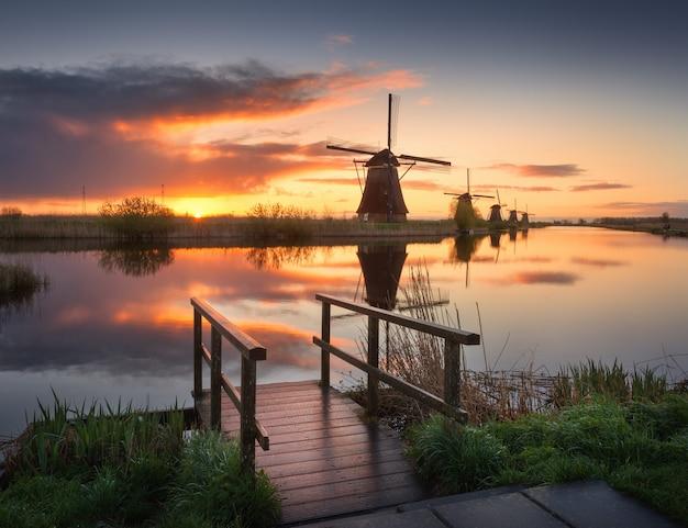 Gestalten sie mit traditionellen holländischen windmühlen bei buntem sonnenaufgang, schöner himmel landschaftlich