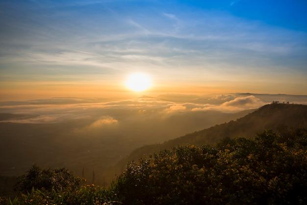 Gestalten sie schöne ansicht des nebeligen nebels des morgensonnenaufgangs landschaftlich, der berg und bunten himmel bedeckt wird