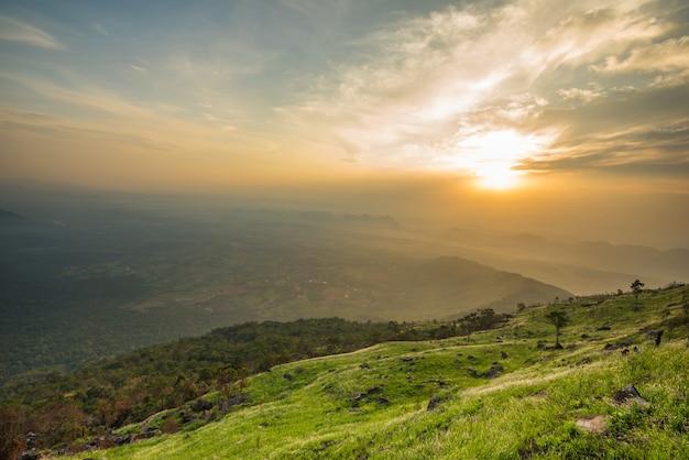 Gestalten sie sonnenaufgang auf dem berg mit blume des grünen grases des feldes und der wiese und schönem wolkenhimmel landschaftlich