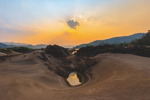 Gestalten sie sonnenuntergang auf dem strand landschaftlich, der mit sommer des felsens und des orange himmels sandig ist