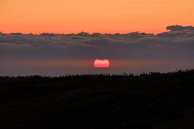 Gestalten sie vom hügel landschaftlich, der mit gras auf dem klaren orange sonnenunterganghimmel mit wolken bedeckt wird