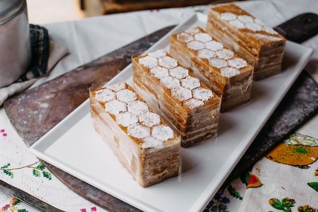 Gestaltete kuchenstücke braune sahne lecker lecker in weißen teller