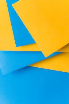 Gestapelt vom gelben und blauen kartenpapierhintergrund