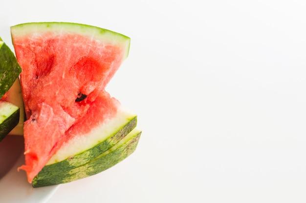 Gestapelt von den dreieckigen scheiben der saftigen wassermelone lokalisiert auf weißem hintergrund