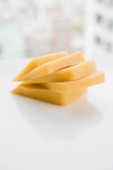 Gestapelt von den käsescheiben auf weißer tabelle