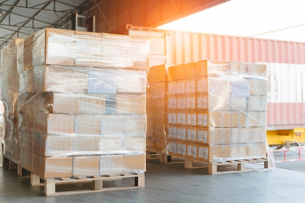 Gestapelt von verpackungskartons, die mit kunststoff umwickelt sind, auf paletten frachtsendungen in der dock-lagerlogistik