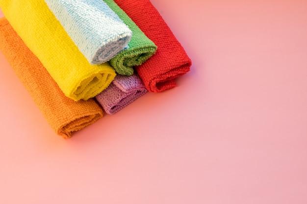 Gestapelte bunte mikrofaser-reinigungstücher auf einem rosa hintergrund. trockene mikrofasertücher für die reinigung verschiedener oberflächen in der küche. kopieren sie platz für text oder logo.