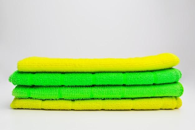 Gestapelte bunte mikrofaser-reinigungstücher auf weißem hintergrund farbige mikrofaser-reinigungstücher studio foto stapel von hellen mikrofasertüchern isoliert auf weißem hintergrund platz für text