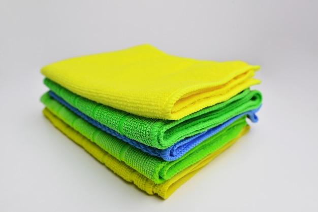 Gestapelte bunte mikrofaser-reinigungstücher auf weißem hintergrund stapel putzlappen oder handtücher reinigungstücher mikrofasertuch gefaltete textil-reinigungsservietten bunter stapel