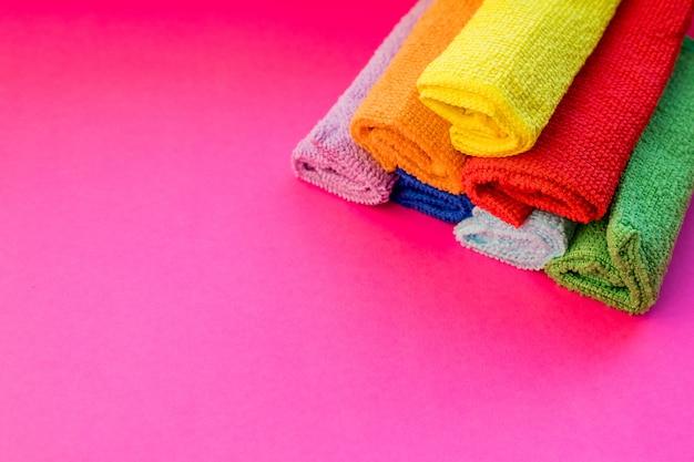 Gestapelte bunte mikrofaser-reinigungstücher. trockene mikrofasertücher für die reinigung verschiedener oberflächen in küche, bad und anderen räumen. kopieren sie platz für text oder logo.