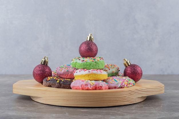 Gestapelte donuts und weihnachtskugeln auf einer holzplatte auf marmoroberfläche