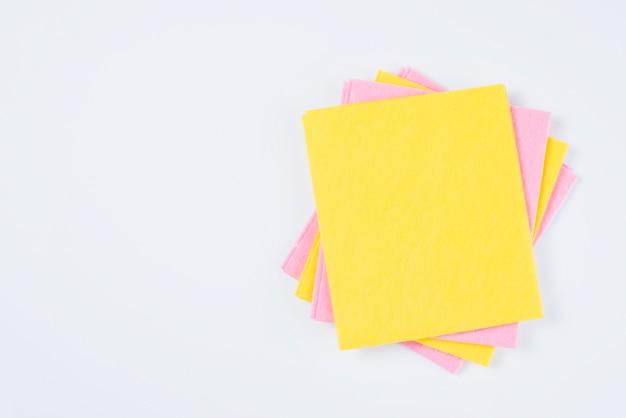 Gestapelte gelbe und rosa farbige staubtücher auf weißem hintergrund