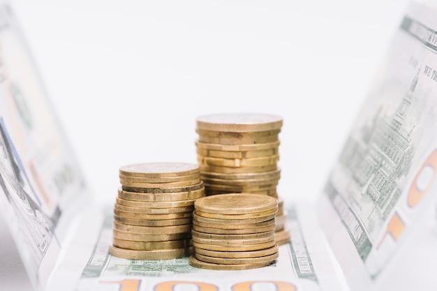 Gestapelte goldene münzen mit banknoten