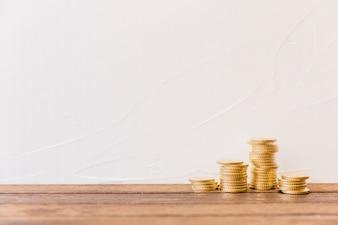 Gestapelte goldene Münzen vor Wand