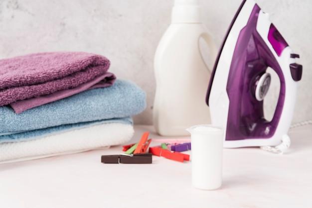Gestapelte handtücher mit weichspüler und eisen