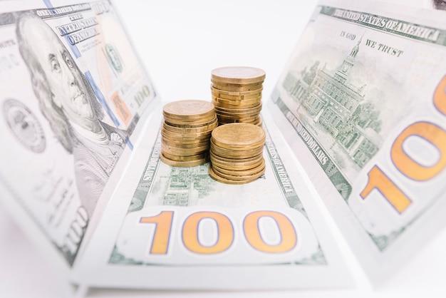 Gestapelte münzen und amerikanische banknoten