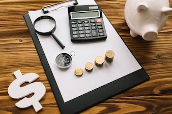 Gestapelte Münzen; Kompass; Vergrößerungsglas und Taschenrechner auf Klemmbrett mit Dollarzeichen und piggybank