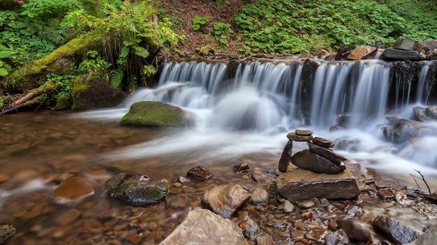 Gestapelte steine auf der seite des gebirgsflusses neben dem wasserfall