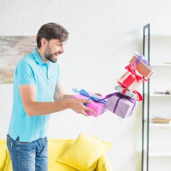 Gestapelte valentinsgrußgeschenke, die von der hand des mannes fallen