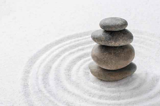 Gestapelte zen-steine sand hintergrundkunst des gleichgewichtskonzepts