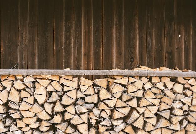 Gestapeltes brennholz vor einer holzhütte in den bayerischen alpen.