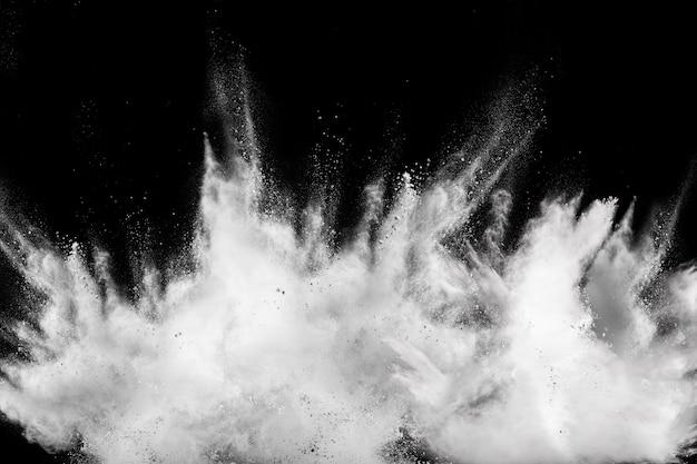 Gestartetes weißes partikelspritzen auf schwarzem hintergrund