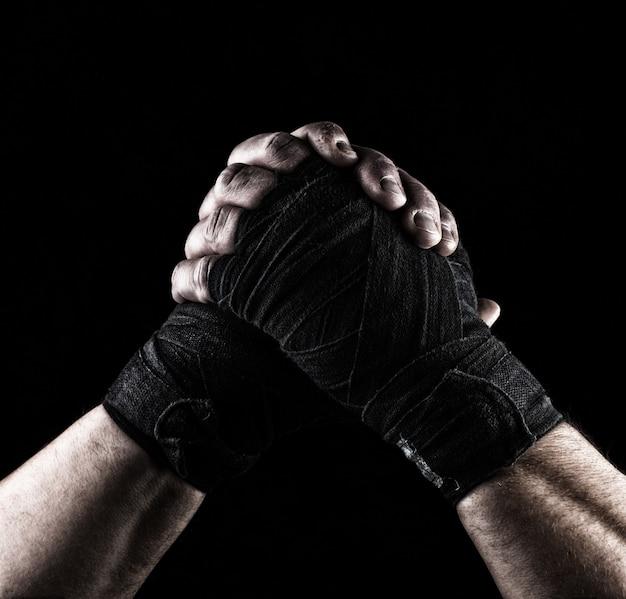 Geste der freundschaft, zwei männliche hände eines athleten mit einem schwarzen textilverband gefesselt
