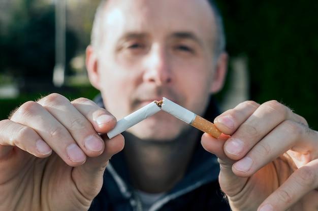 Geste für das rauchen aufzuhören, anti rauchen, männliche hand zerquetschende zigarette, nichtraucher. mann hat beschlossen, mit dem rauchen aufzuhören.