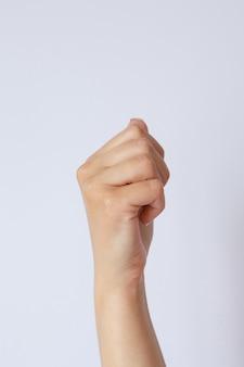 Geste und zeichen, frauenhand hält etwas an einer hellen wand