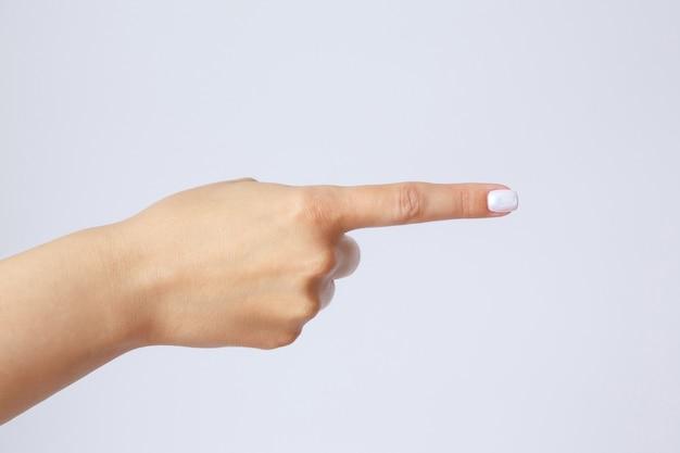 Geste und zeichen, weibliche hand auf einer weißen wand. finger zeigen