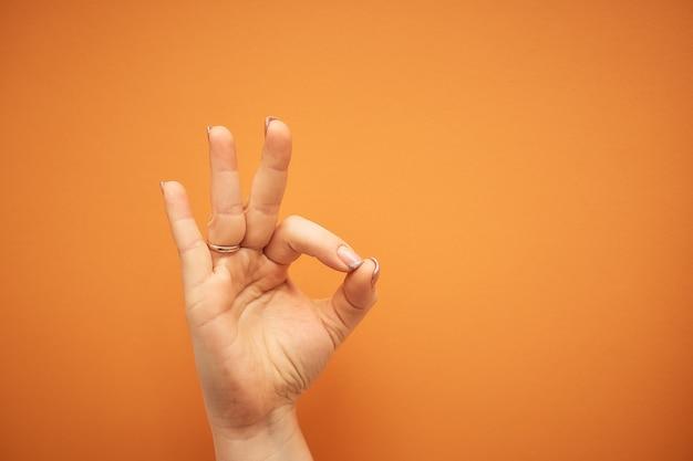 Geste, weibliche hand zeigt ok-zeichen auf orange isoliert.