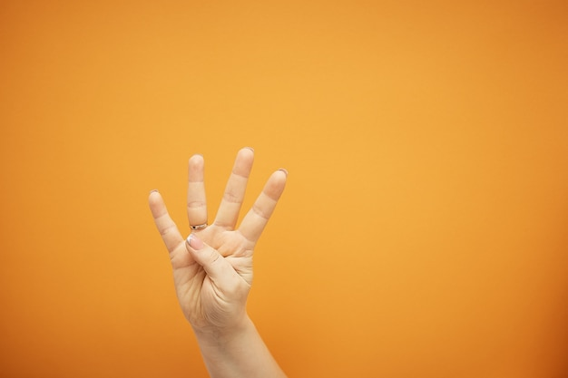 Geste, weibliche hand zeigt vier finger auf orange isoliert.