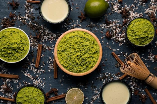 Gestell aus schalen mit grünem pulver und teetassen