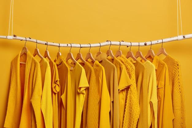 Gestell mit gelber kleidung nach der chemischen reinigung. kleiderschrank mit verschiedenen outfits für verschiedene jahreszeiten. damenmode im modegeschäft. selektiver fokus. leerzeichen oben.