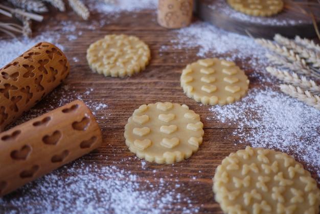 Gestempelte kekse mit einem druck von herzen und schmetterlingen. hölzerne nudelhölzer für kekse