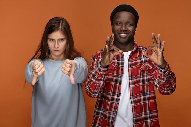 Gesten-, symbol- und zeichenkonzept. emotionales interraciales paar, das kontroverse haltung ausdrückt - schwarzer mann, der lächelt und ok geste macht, während verärgerte wütende weiße frau daumen nach unten zeigt