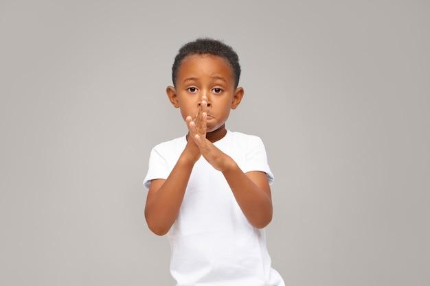 Gesten, zeichen, symbole und körpersprache. porträt des bezaubernden entzückenden entzückenden afroamerikanischen kleinen jungen, der beiläufig gekleidet ist und isolierte kreuzende hände vor ihm aufstellt, tanzt und neue bewegungen zeigt