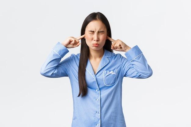 Gestörte dumme asiatische mädchen in blauen pyjamas hassen störende geräusche, schloss ohren und augen und verzog unbefriedigt das gesicht, beschwerte sich über lautes geräusch, sah verärgert aus, eine schlechte übernachtungsparty zu haben, weiße wand