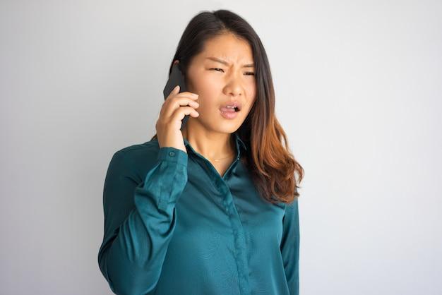 Gestörte junge asiatin in der freizeitkleidung, die am telefon spricht.