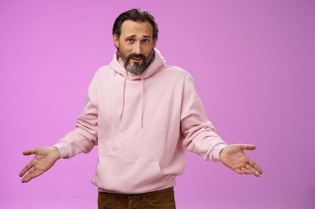 Gestörte verwirrte reife erwachsene bärtige mann graue haare in rosa hoodie argumentieren blick sauer beleidigt achselzucken gespreizte hände seitwärts bestürzung blick ahnungslose kamera fragen warum, lila hintergrund.
