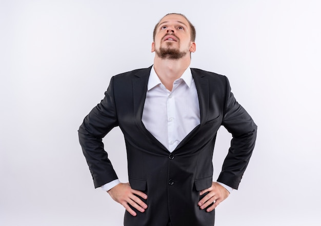 Gestörter hübscher geschäftsmann, der anzug trägt, der oben über weißem hintergrund steht