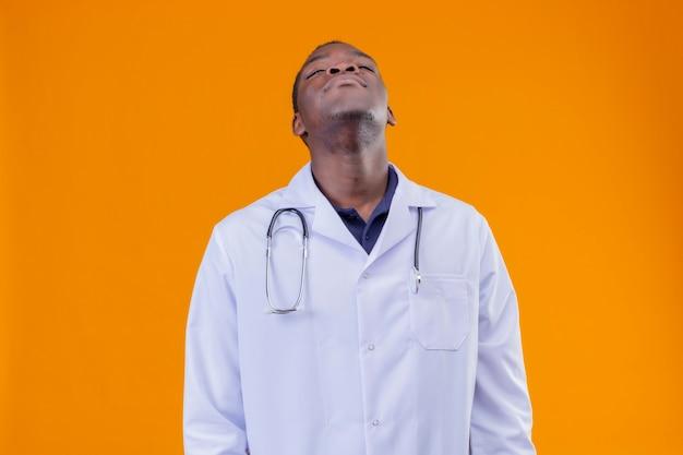 Gestörter junger afroamerikanerarzt, der weißen kittel mit stethoskop mit geschlossenen augen trägt
