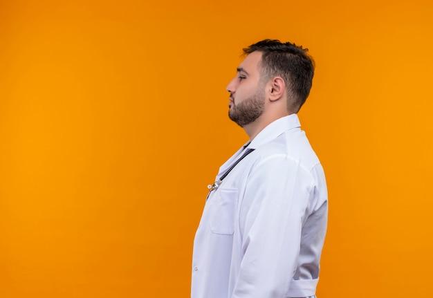 Gestörter junger bärtiger männlicher arzt, der weißen kittel mit stethoskop seitwärts trägt