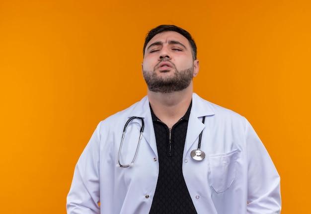 Gestörter junger bärtiger männlicher arzt, der weißen kittel mit stethoskop trägt, das müde und gestresste schließende augen sieht